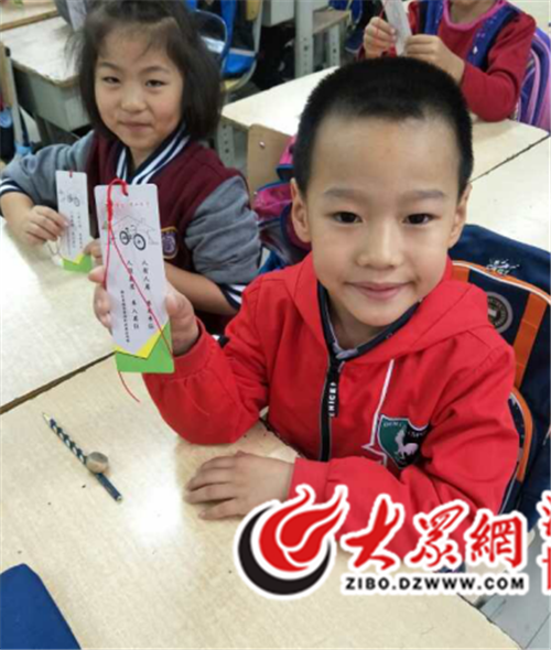 人员将宣传书签发给每位小朋友-桓台城管执法局开展非机动车管理