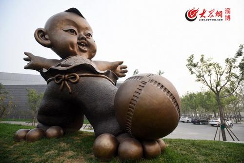伫立在博物馆门口的雕塑蹴鞠娃源源(徐建彬 摄)